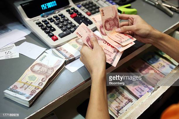An employee handles Thai onehundred baht banknotes as banknotes of other denominations sit inside a drawer at a Super Rich 1965 Co currency exchange...