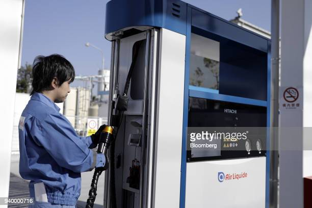 An employee handles the nozzle of a hydrogen pump during a demonstration at the Kawasaki Hydrogen Station operated by Air Liquide Japan Ltd in...