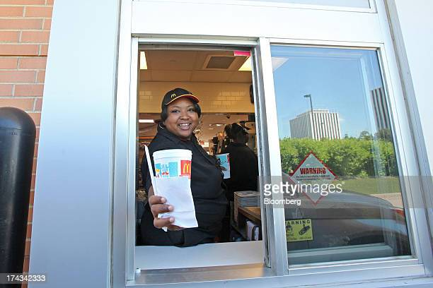 An employee hands a drivethru customer an order at a McDonald's Corp restaurant in Oak Brook Illinois US on Friday July 12 2013 Don Thompson...