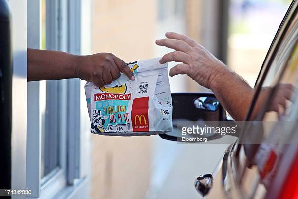 An employee hands a drivethru customer his order at a McDonald's Corp restaurant in Oak Brook Illinois US on Friday July 12 2013 Don Thompson...