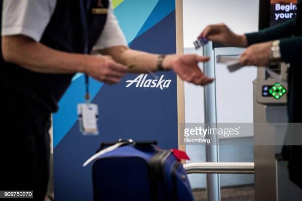 An employee hands a traveler a boarding pass at an Alaska Air Group Inc checkin counter at the San Francisco International Airport in San Francisco...