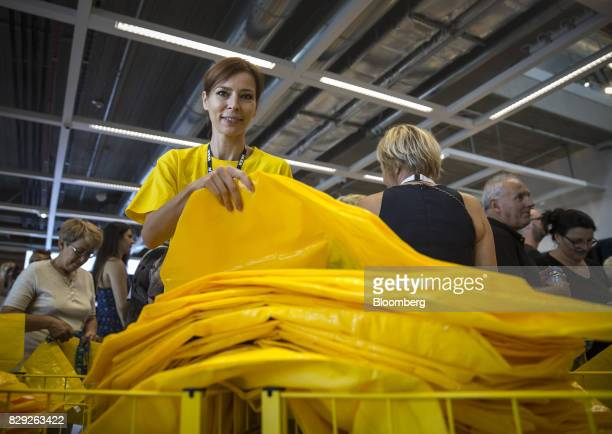 An employee hands out yellow IKEA shopping bags to arriving customers on the opening day of IKEA of Sweden AB's first department store in Belgrade...