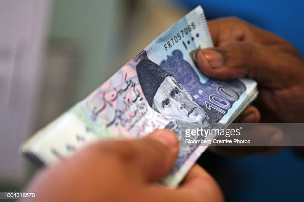 an employee hands over a bundle of pakistan rupee banknotes - pakistan stock pictures, royalty-free photos & images