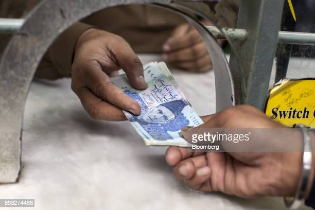 An employee hands over Pakistani onethousand rupee banknotes at a cash counter of the office of Pakistan Currency Exchange Pvt in Karachi Pakistan on...