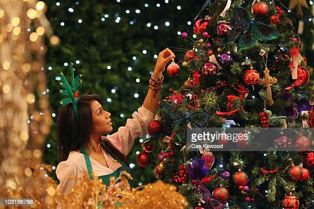 An employee hangs a decoration on a tree in the Christmas shop at Selfridges department store on August 2, 2010 in London, England. Selfridges...