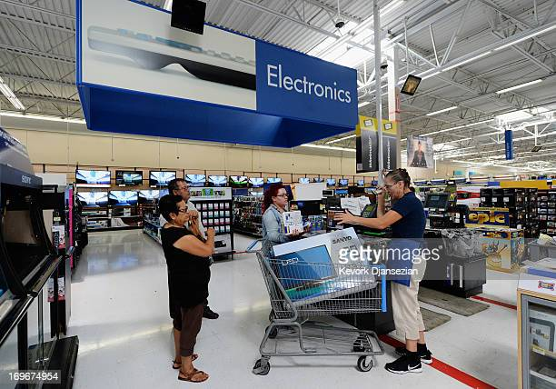 An employee help customers in the electronics section of Walmart Supercenter store on May 30 2013 in Pico Rivera California Walmart is the largest...