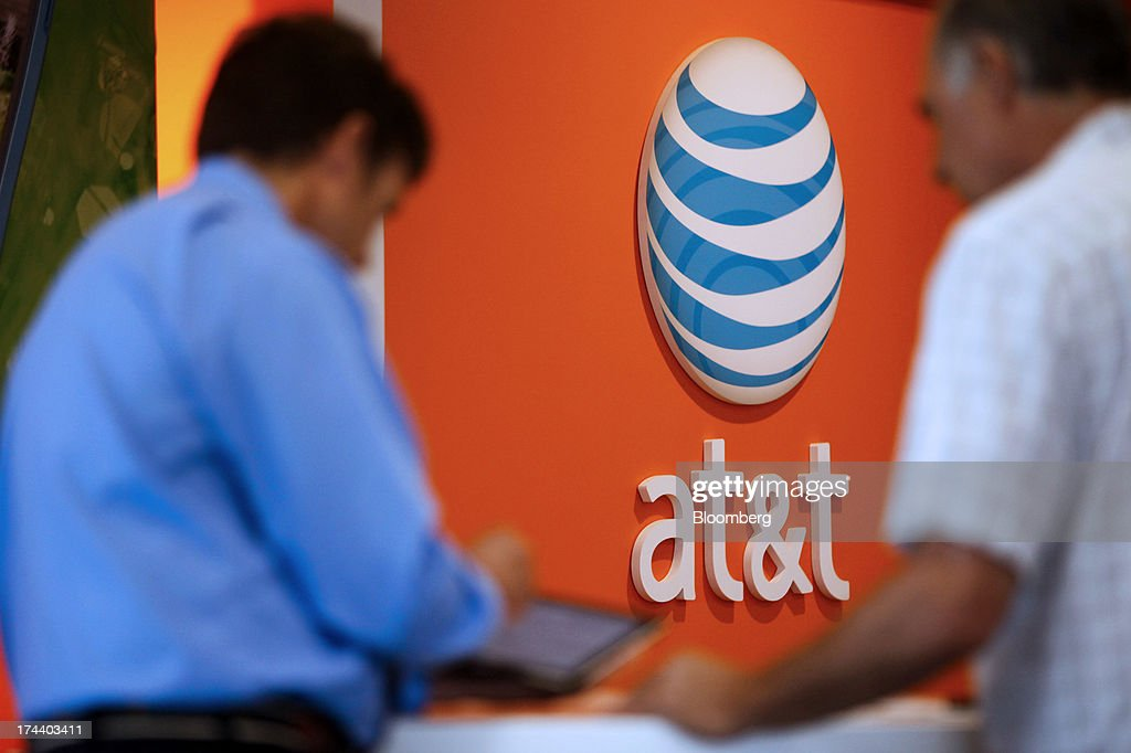 An employee helps a customer at an AT&T Inc. store in Manhattan Beach, California, U.S., on Monday, July 22, 2013. AT&T Inc. is scheduled to release earnings figures on July 23. Photographer: Patrick T. Fallon/Bloomberg via Getty Images