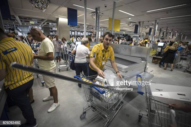 An employee helps a customer load goods onto a conveyor belt at the checkout desk on the opening day of IKEA of Sweden AB's first department store in...