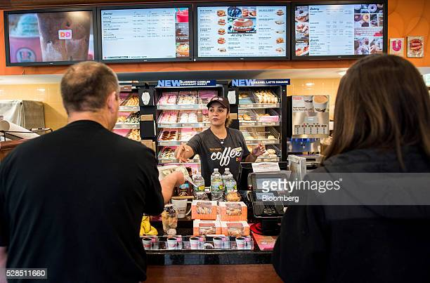 An employee helps customers at a Dunkin' Donuts Inc location in Ramsey New Jersey US on Thursday May 5 2016 Dunkin' Brands Group Inc a leading...
