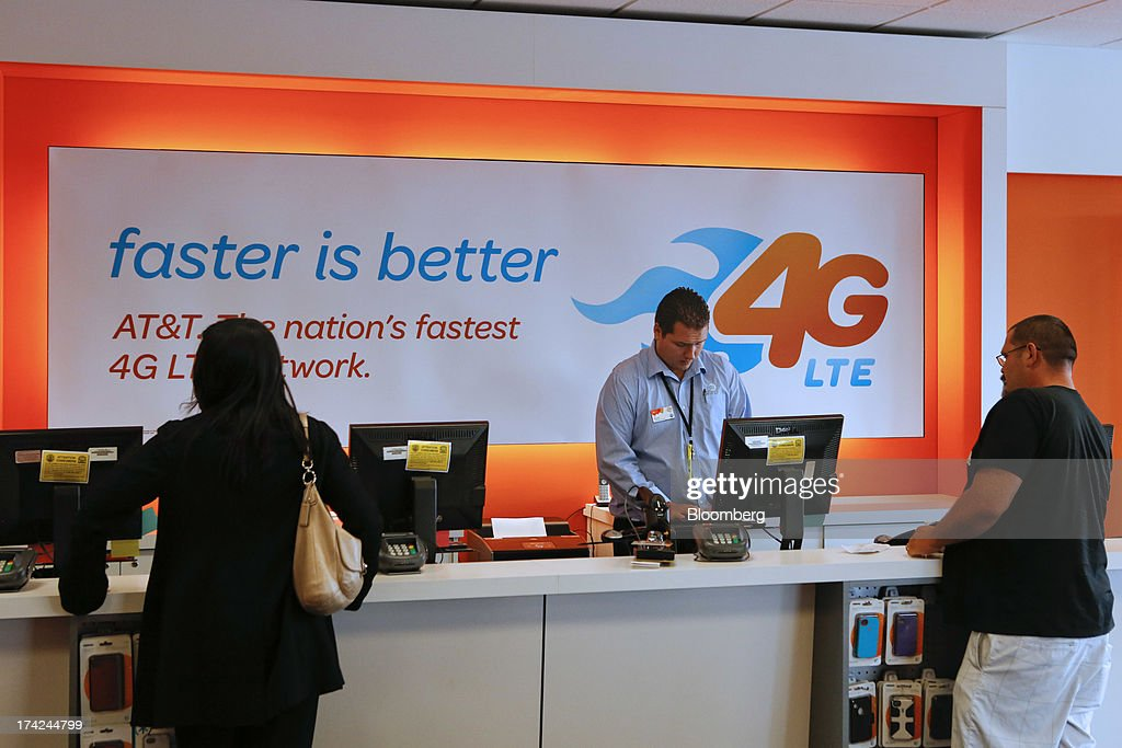 An employee helps customers at an AT&T Inc. store in Manhattan Beach, California, U.S., on Monday, July 22, 2013. AT&T Inc. is scheduled to release earnings figures on July 23. Photographer: Patrick T. Fallon/Bloomberg via Getty Images