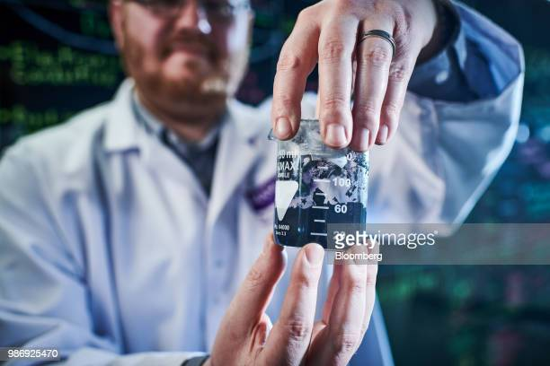 An employee holding a beaker of graphene slurry containing graphene and polymer binders poses for a photograph inside a laboratory at the National...