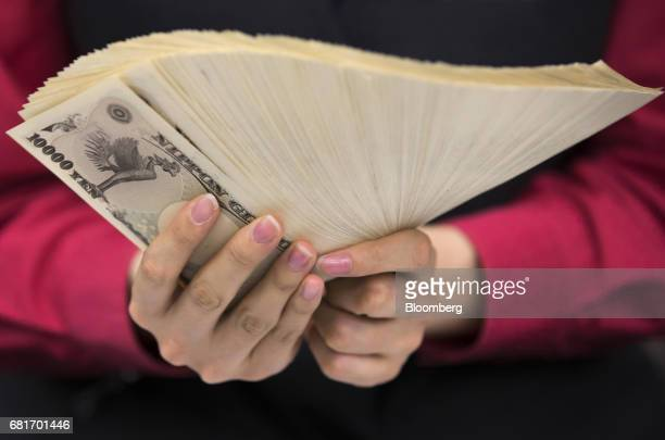 An employee holds 10000 yen banknotes for a photograph at the Mizuho Bank Ltd branch inside the Mizuho Financial Group Inc headquarters in Tokyo...