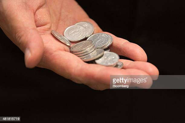 An employee holds 1yen coins of change at a McDonald's restaurant operated by McDonald's Holdings Co Japan Ltd in Tokyo Japan on Tuesday April 1 2014...