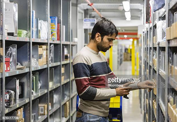 An employee holds a barcode scanner while collecting items for customers' delivery orders inside an Amazoncom Inc fulfillment center in Koblenz...
