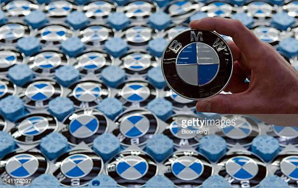 An employee holds a Bayerische Motoren Werke AG badge in this arranged photograph at the company's assembly plant in Regensburg Germany on Monday...