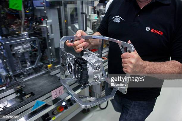 An employee holds a Bosch iBooster autonomous automobile braking assistance component at the Robert Bosch GmbH plant in Blaichach Germany on Tuesday...