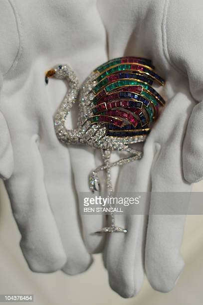 An employee holds a Cartier flamingo diamond clip from 1940 at Sotheby's auctioneers in London on September 23 2010 The clip is expected to fetch...