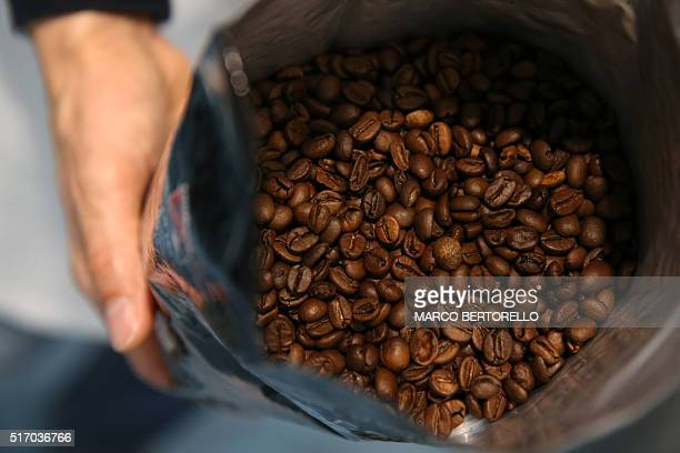 An employee holds a coffee pack in the Luigi Lavazza coffee factory on March 22 2016 in Turin / AFP / MARCO BERTORELLO