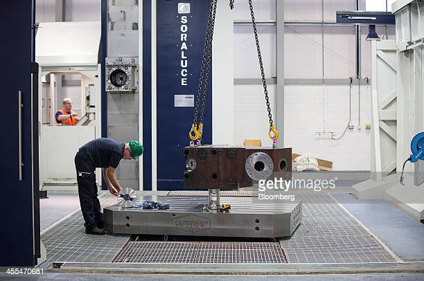 An employee holds a component of a subsea gas and oil rig tree as it is constructed at the General Electric Co manufacturing plant in Montrose UK on...