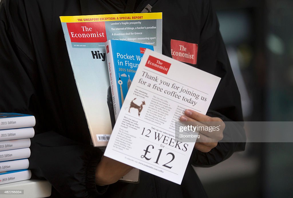 An employee holds a copy of The Economist magazine and a subscription information leaflet at a news kiosk in London, U.K., on Wednesday, July 29, 2015. Pearson Plc moved closer to an exit from business publishing as it announced plans to dispose of its stake in the 172-year-old Economist magazine, just days after the sale of the Financial Times newspaper. Photographer: Simon Dawson/Bloomberg via Getty Images