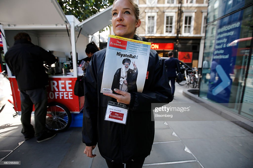 An employee holds a copy of The Economist magazine beside a Kopi Luwak Civet coffee vending stall in London, U.K., on Wednesday, July 29, 2015. Pearson Plc moved closer to an exit from business publishing as it announced plans to dispose of its stake in the 172-year-old Economist magazine, just days after the sale of the Financial Times newspaper. Photographer: Simon Dawson/Bloomberg via Getty Images