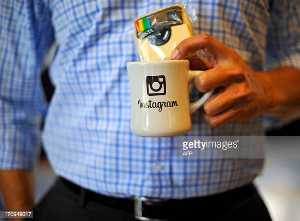 An employee holds a cup with the Instagram logo at Facebook's corporate headquarters during a media event in Menlo Park California on June 20 2013...