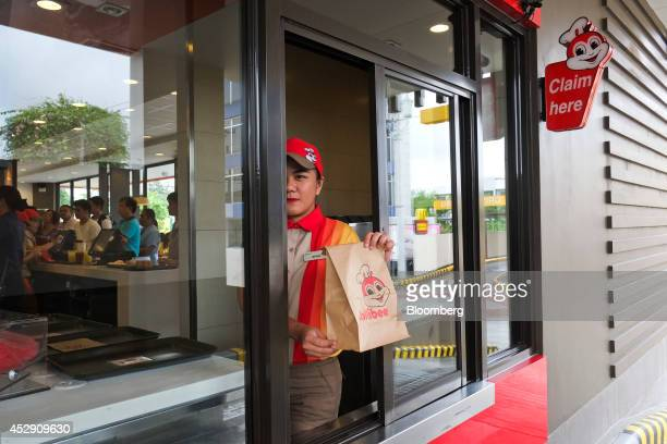 An employee holds a customer's order ready for collection in the drivethrough section of a Jollibee Foods Corp restaurant in Quezon City Metro Manila...