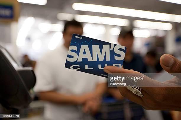 An employee holds a custumer's Sam's Club inside a store in the Toreo neighborhood of Mexico City Mexico on Friday Nov 18 2011 WalMart de Mexico SAB...