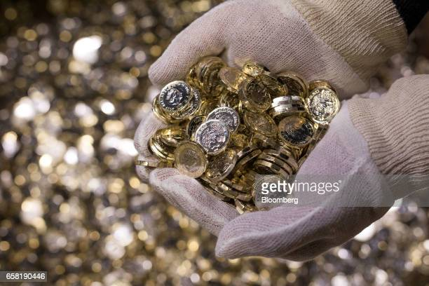 An employee holds a handful of new British one pound coins during their production at The Royal Mint in Llantrisant UK on Thursday March 23 2017...