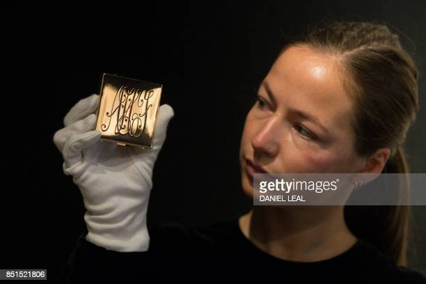 An employee holds a monogrammed powder compact Ciardetti Firenze 1950s with a reserve price of £2000 £3000 during a preview of Audrey Hepburn's...