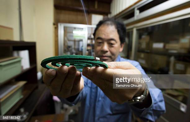 An employee holds a mosquito coil for a photograph as he inspects it in a laboratory at the Kishu Factory of Dainihon Jochugiku Co. Ltd. On July 6,...