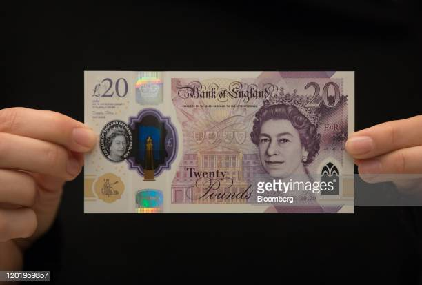 An employee holds a new 20pound banknote featuring Britain's Queen Elizabeth II during an event to mark its circulation at the Tate Britain art...