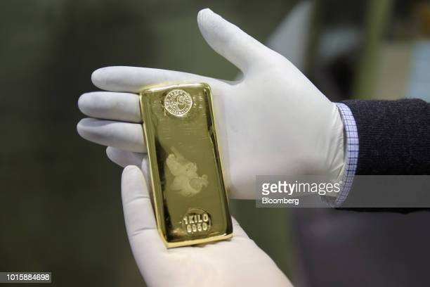An employee holds a one kilogram gold bar for a photograph at the Perth Mint Refinery operated by Gold Corp in Perth Australia on Thursday Aug 9 2018...