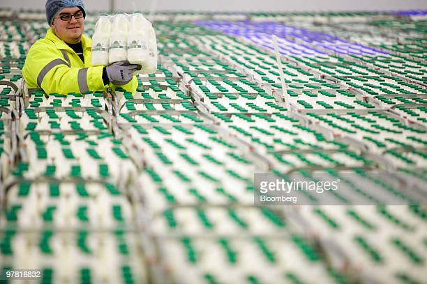 An employee holds a package of milk bottles at the Dairy Crest factory in Foston UK on Wednesday March 17 2010 Dairy Crest Group Plc said pretax...