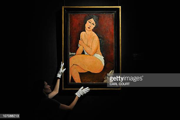An employee holds a painting dated 1917 and entitled 'Nu Assis Sur Un Divan' by Amedeo Modigliani at Sotheby's auction house in London England...