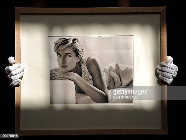 An employee holds a photograph of Princess Diana by Peruvian photographer Mario Testino taken in 1993 which is expected to reach £2000030000 in...