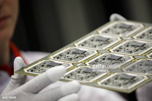 An employee holds a sheet of automated driving Advanced Radar sensor mainboard computer circuit components on the production line at the Continental...