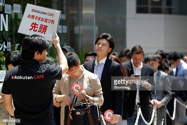 An employee holds a sign as customers wait in line for the opening of the Rakuten Cafe operated by Rakuten Inc in Tokyo Japan on Thursday May 29 2014...