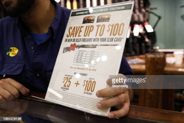 An employee holds a sign notifying Club Card members of discounts on new or used firearms at a Bass Pro Outdoor World LLC store on Black Friday in...