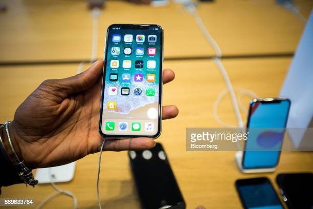 An employee holds an iPhone X smartphone while assisting a customer during the sales launch at a store in New York US on Friday Nov 3 2017 The $1000...