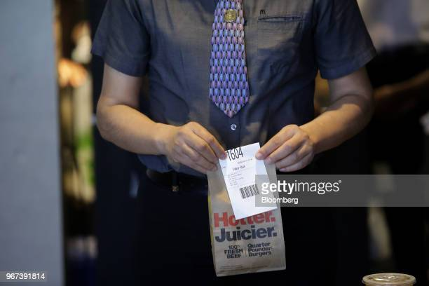 An employee holds an order at the restaurant inside the new McDonald's Corp headquarters in Chicago Illinois US on Monday June 4 2018 McDonald's CEO...