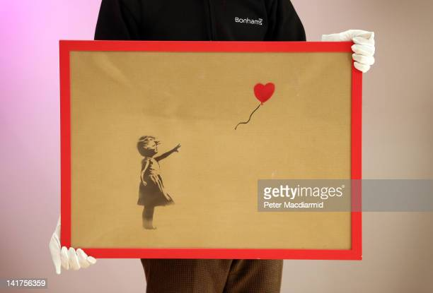An employee holds Banksy's 'Girl and Balloon' which was painted on an Ikea frame at Bonhams auctioneers on March 23 2012 in London England The...