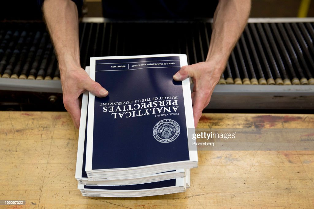 An employee holds copies of the Fiscal Year 2014 Budget at the U.S. Government Printing Office in Washington, D.C., U.S., on Monday, April 8, 2013. Less than a week after job-creation figures fell short of expectations and underscored the U.S. economy's fragility, President Barack Obama will send Congress a budget that doesn't include the stimulus his allies say is needed and instead embraces cuts in an appeal to Republicans. Photographer: Andrew Harrer/Bloomberg via Getty Images