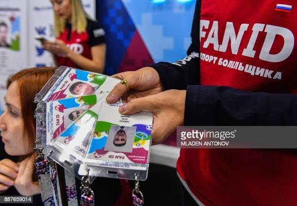 An employee holds FAN IDs for the 2018 FIFA World Cup Russia at a distribution center in Moscow on December 7 2017 / AFP PHOTO / Mladen ANTONOV