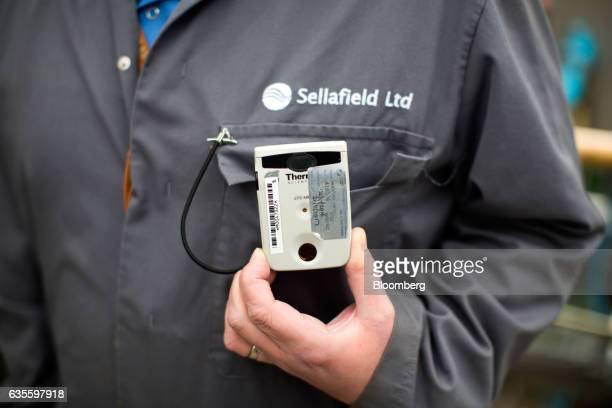 An employee holds his Electronic Personal Dosimeter used to monitor radiation exposure at Sellafield atomic fuel reprocessing site operated by...