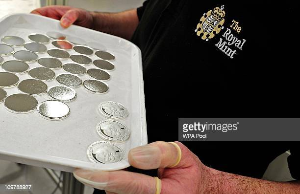 An employee holds newly minted official Royal Wedding coins at the Royal Mint in Cardiff March 5 2011 The new five pound coin is being made to...