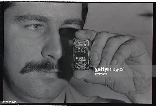 An employee holds one of the Bache Halsey 10ounce gold bars stamped with the lot number that has been manufactured at the Johnson Matthey Ltd plant...