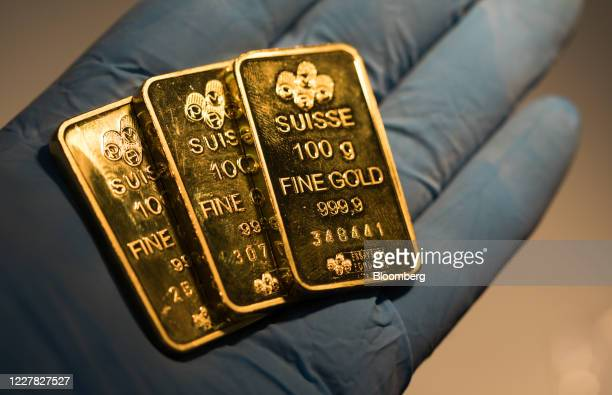 An employee holds one-hundred gram gold bars at Gold Investments Ltd. Bullion dealers in this arranged photograph in London, U.K., on Wednesday, July...