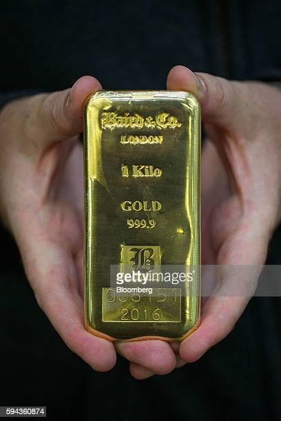 An employee holds out a one kilo 9999 fine gold bar at the Baird Co Ltd precious metals refinery in London UK on Wednesday Aug 3 2016 Baird Co which...