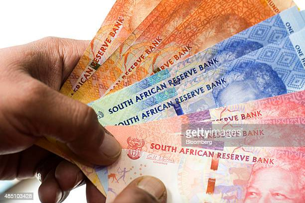 An employee holds South African Rand notes in this arranged photograph in London UK on Monday Aug 24 2015 South Africa's rand tumbled the most since...